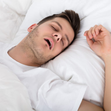 View Of Tired Young Man Snoring While Deep Sleeping In Bed